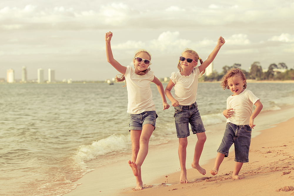 Three happy children dancing on the beach